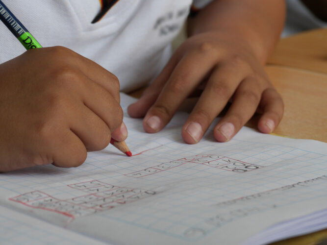 child hands writing in math notebook