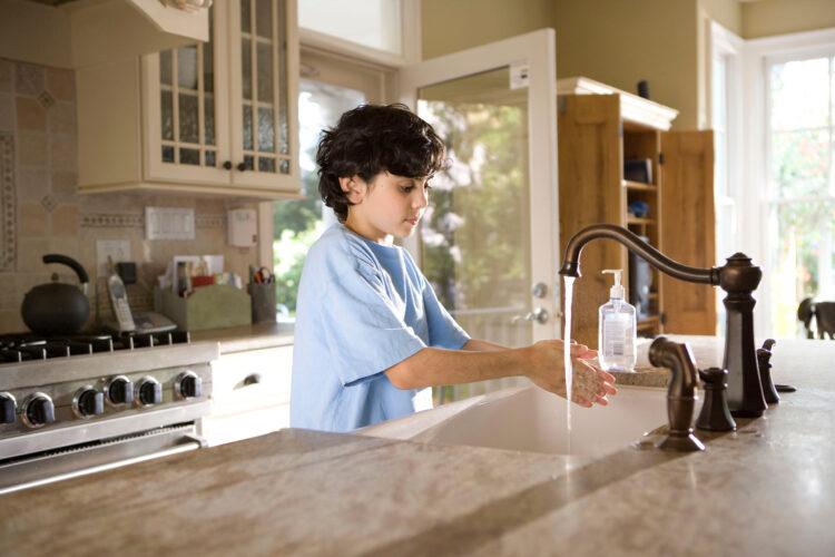 child washing hands in kitchen