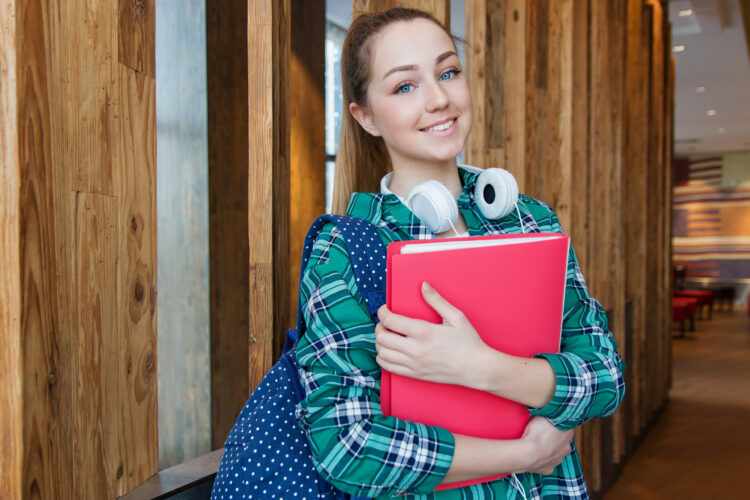 smiling teen with headphones and red notebook